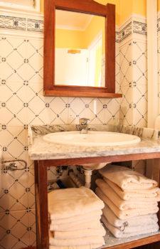 Waschbecken in blau weiss gefliesstem Bad, darunter Regal mit Handtuchstapeln darüber Holzspiegel