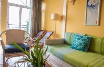 Wohnzimmer Couch mit grüner Auflage und Polster, weisser Sessel mit blauem Polster, zwei Liegestühle und eine Lampe im Hintergrund