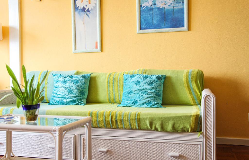 Weiße Couch mit grüner Auflage darauf zwei Pölster davor ein Glastisch mit einer Zimmerpflanze