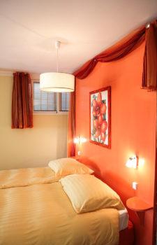 Doppelbett mit gelben Bezug vor oranger Wand