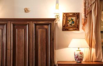 Kasten und Lampe daneben haengt ein gerahmtes Bild