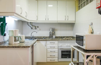 Küche weiß mit Spüle, Herd, Mikrowelle, Toaster und anderen Küchengeräten