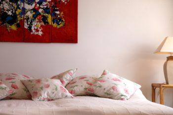 Mehrere Poelster liegen auf einem Bett