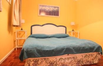 Bequemes Doppelbett mit dunkelblauer Decke vor einer gelben Wand