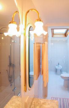 Spiegel darueber eine Bluetenfoermige Lampe