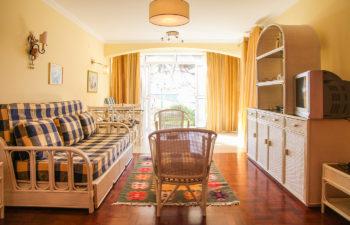 Wohnzimmer mit Couch, Tisch, Sesseln und Fernsehmöbel