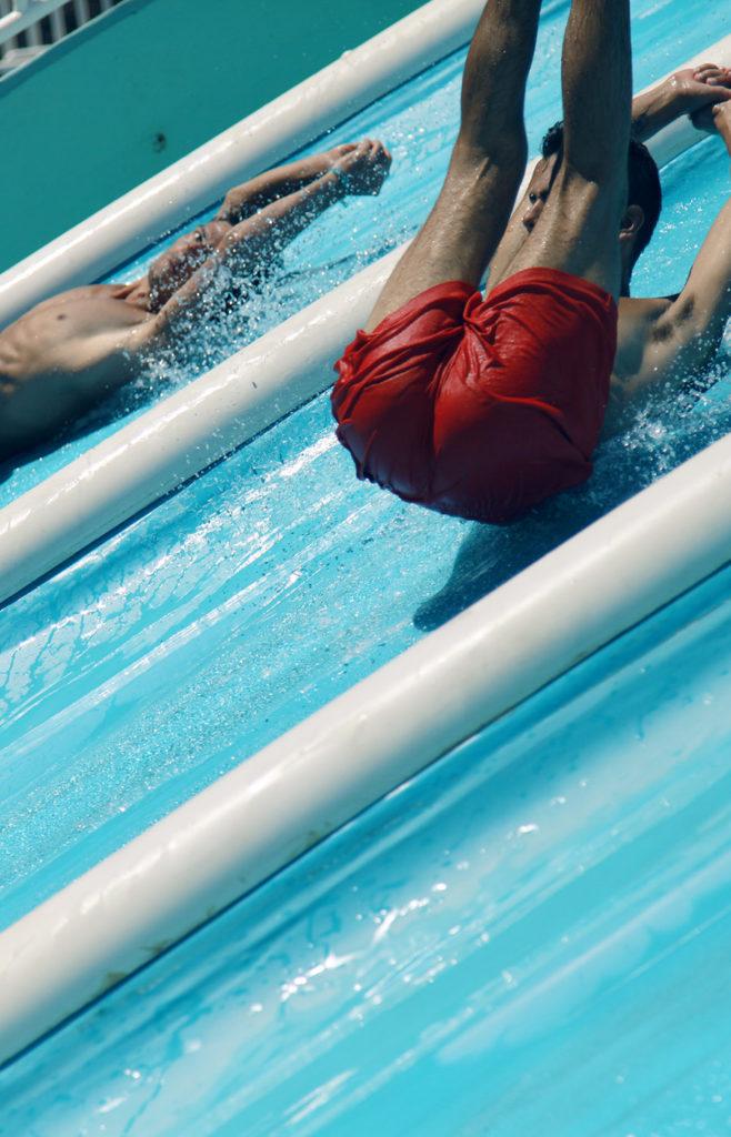 Mann mit roter Badehose auf Rutsche