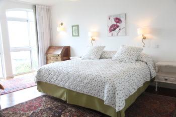 Doppelbett mit grün-weißer Decke von vorne