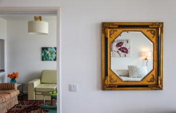 Spiegel mit Goldrahmen daneben ein Durchgang zum Wohnzimmer