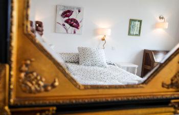 Spiegel in dem sich das gemütliche Doppelbett spiegelt