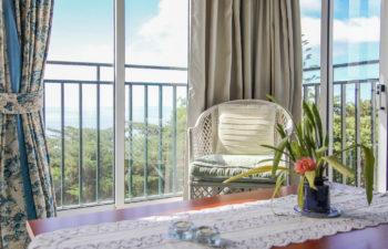 Gemütlicher Sessel vor einem Fenster mit Ausblick auf das Meer